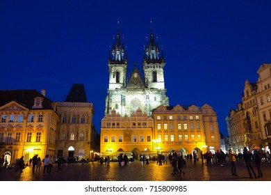 PRAGUE, CZECH REPUBLIC – FEBRUARY 26, 2017: Crowds mill around Prague's Old Town Square in front of the illuminated Tyn Church at night.