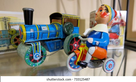 PRAGUE, CZECH REPUBLIC – FEBRUARY 26, 2017: Old-fashioned metal toys, including a train and an elf riding a bicycle, on a shop shelf in Prague, Czech Republic