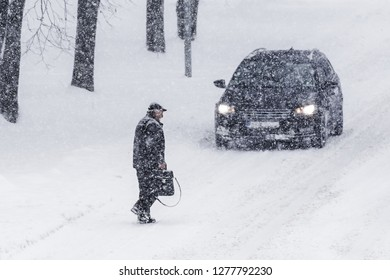 Prague, Czech Republic - Januar 2019 / A man walking across a path in a snow blizzard. In the background standing car. Frosty winter weather.