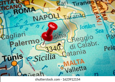 PRAGUE, CZECH REPUBLIC - JANUARY 12, 2019: Red thumbtack in a map. Pushpin pointing at Palermo city on the island Sicily in Italy.