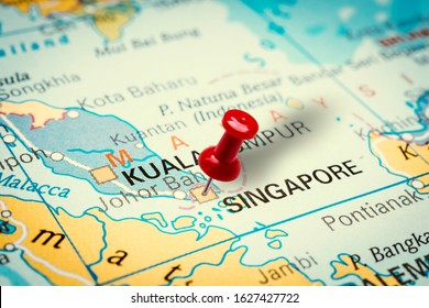 PRAGUE, CZECH REPUBLIC - JANUARY 12, 2019: Red thumbtack in a map. Pushpin pointing at Singapore city in Singapore.