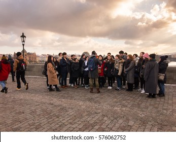 PRAGUE, CZECH REPUBLIC - JANUARY 17: Group of Chinese tourists on guided tour, Charles Bridge, Prague. In Prague, Czech Republic. On 17th January 2017.