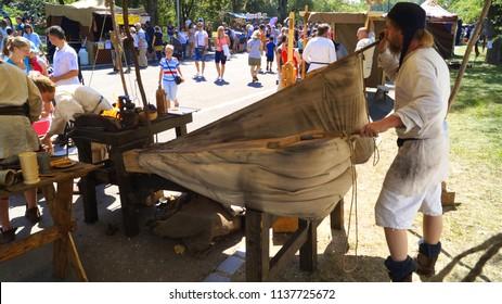 Prague, Czech Republic - July 14, 2018 - A man in antique clothes blows out large antique blacksmiths for forging metal in Prague
