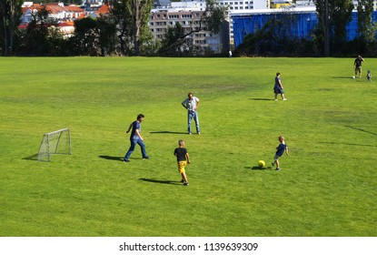 Prague, Czech Republic - July 14, 2018 - Children and adults playing football in the park of Prague