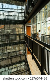 PRAGUE, CZECH REPUBLIC - JULY 2018: Guest walking along a balcony inside the atrium of the NH Prague City Hotel. The balconies are eflected in the glass wall on the left.
