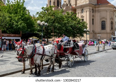 Prague, Czech Republic Jun. 09. 2018: Horse pulled  carriage awaiting for tourists at Church of St. Nicholas  Square  Church.