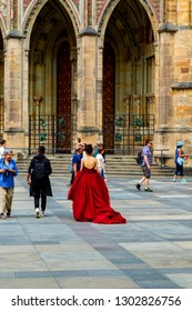 Prague Czech Republic Jun 8 2018: Lady in red dress walking in The Royal Castle and St. Vitus Cathedral. Major destination for many tourists, also UNESCO heritage.