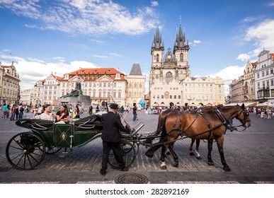 PRAGUE, CZECH REPUBLIC - JUNE 15, 2014: Tourists on horse carriage at the Old Square in Prague. Old Town Square is a historic square in the Old Town quarter of Prague.