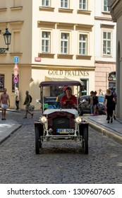 Prague, Czech Republic - June 19, 2018: A vintage red car driving down the street in Prague near Old Town