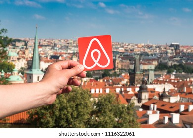 Prague, Czech Republic. June, 2018.  Travel around the world with Airbnb. Logo Airbnb and the city on the background. Home concept. Man holds the logo of a popular company.