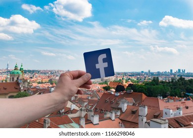 Prague, Czech Republic. June, 2018. Logo Facebook and the city on the background. Concept. Man holds the logo of a popular company.