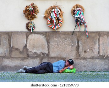 Prague, Czech Republic - June, 2018: Homeless man sleeping on the street in the downtown. Withered traditional Christmas wreaths intertwined with ribbons of red, white, green colors on the wall