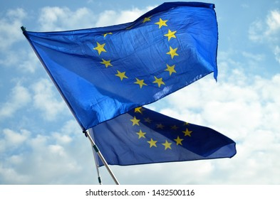 Prague / Czech Republic - June 23 2019:  Two European Union (EU) Flags waving in the wind against blue sky with white clouds