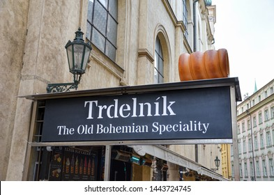 Prague, Czech Republic - June 27th 2019: Sign of street stand selling trdelnik - traditional Czech dessert and popular Bohemian dish. Tasty cake, bakery. Sweet roll with filling.