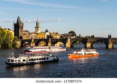 PRAGUE, CZECH REPUBLIC - JUNE 30, 2018: Boats on the Moldovia river near the Charles Bridge.