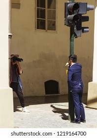 PRAGUE, CZECH REPUBLIC - JUNE 30, 2018: Foreign tourists making photo shoot in The Old Town of Prague (Stare Mesto)