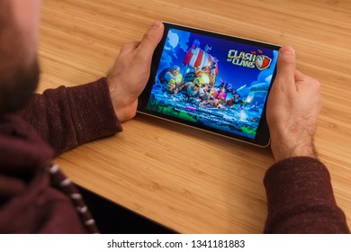 PRAGUE, CZECH REPUBLIC - MARCH 16, 2019: Man holding a smartphone and playng the Clash of Clans mobile game. An illustrative editorial image on an bamboo background.