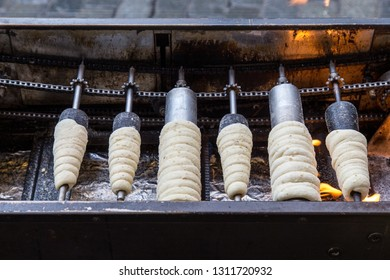 Prague, Czech Republic - March 18, 2017: Famous Czech pastry Trdelnik being baked in a street bakery. Trdelnik, also called Trdlo is a sugary sweet pastry.