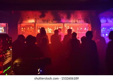 PRAGUE, CZECH REPUBLIC - March 22 2019: Silhouettes of people in the dark bar of the FUCHS2 music club during the Zizkovska Noc 2019 (Czech: Žižkovská Noc 2019) festival. Haze.