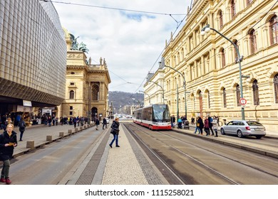PRAGUE, CZECH REPUBLIC - MARCH 24, 2018: People walking on sidewalk and cars riding on road. Red tram waiting for passengers. Bright sun reflecting on old architecture buildings