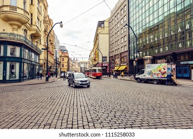 PRAGUE, CZECH REPUBLIC - MARCH 24, 2018: People walking on sidewalk. Cars and old tram riding on road. Bright sun reflecting on old architecture buildings