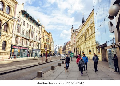 PRAGUE, CZECH REPUBLIC - MARCH 24, 2018: People walking on sidewalk and cars riding on road. Bright sun reflecting on old architecture buildings
