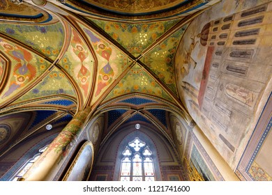 PRAGUE, CZECH REPUBLIC - MARCH 25, 2018: Neo-gothic interior of Basilica of St. Peter and St. Paul. Vysehrad castle complex. Drawings on walls and ceiling. Glowing windows