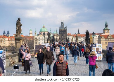 Prague, Czech Republic, March 27, 2018: tourists walking and take pictures at Charles bridge.