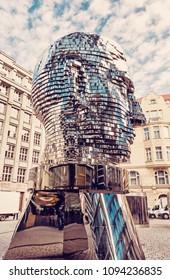 PRAGUE, CZECH REPUBLIC â?? MARCH 9, 2018: Moving statue of Franz Kafka in Prague, Czech republic. Artistic symbolic object. Architectural theme. Illustrative editorial. Red photo filter.