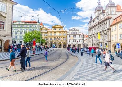 Prague, Czech Republic, May 13, 2019: people are walking crossing tram tracks on Malostranske namesti square in Prague city near Sternberg palace in Lesser Town (Mala Strana) district, Bohemia
