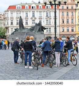 PRAGUE, CZECH REPUBLIC - May 2, 2019: An organized group of tourists on bicycles rented, accompanied by a guide on the city square.