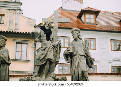 Prague, Czech Republic - May 2014. Sculpture of the Holy Savior with Cosmas and Damian, the holy healers on the Charles Bridge on the background of red roofs and a flying black crow.