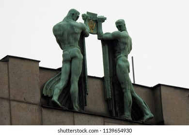 Prague, Czech Republic, May 24, 2018. Weather-Beaten Sculpture of two Handsome, Naked Men on Top of a Building in Prague