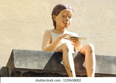 Prague, Czech Republic, May 25, 2018. Weather-Beaten Sculpture of a Little Girl sitting high up on a Ledge at the Clementinum in Prague