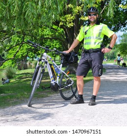 PRAGUE, CZECH REPUBLIC - May 25, 2019:  A police officer on police bicycle on patrol of the park area.
