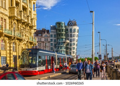 PRAGUE, CZECH REPUBLIC - MAY 3, 2017: Prague people and tram in the town street near Dancing modern house Fred and Ginger