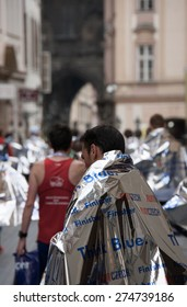 PRAGUE, CZECH REPUBLIC - MAY 3, 2015: Runners who have just finished the Volkswagen Prague Marathon walk from the finish of the marathon in the Old Town Square, the famous place in Prague