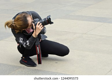 PRAGUE, CZECH REPUBLIC - May 4, 2018: The girl with the camera bent to obtain the desired angle of the image. The world through the eyes of a girl