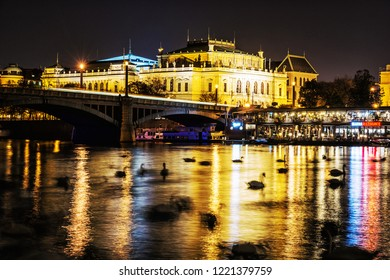 PRAGUE, CZECH REPUBLIC – NOVEMBER 1, 2018: Rudolfinum - Czech philharmonic in Prague with restaurant in boat and swans in Vltava river, Czech republic. Night scene. Illustrative editorial.