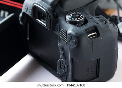 Prague, Czech republic - November 14, 2018: Rear side of Canon EOS 750D DSLR camera in black silicone protective case with back buttons, viewfinder, mode selection dial, and display visible