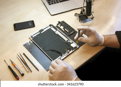 Prague, Czech Republic - NOVEMBER 21, 2014: Photo of the repair process of an iPad Air and iPhone 4. IPad Air and iPhone 4 are produced by Apple Computer, Inc..