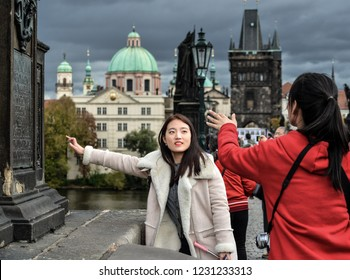Prague, Czech Republic - October 10, 2017: Pretty asian girl poses for selfie and looks at the old city of Prague and Vltava river from The Charles Bridge, Prague Czech Republic