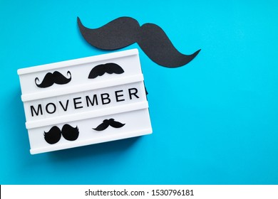 Prague, Czech Republic - October 12, 2019: Ligth box with Movember slogan and black moustache on blue background.