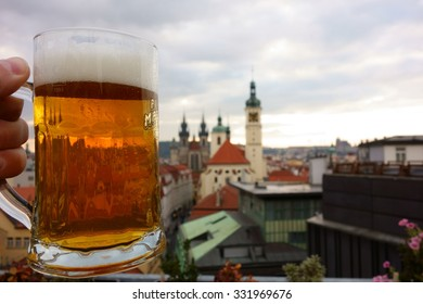 PRAGUE, CZECH REPUBLIC - OCTOBER 19, 2015: A pint of Czech craft beer on a rooftop terrace in the center Prague, Czech Republic with many of the city's landmarks appearing on the background in 2015.