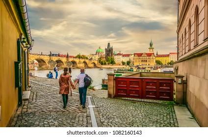 Prague, Czech Republic - October 2 2017: A couple walks toward the riverbank and Charles Bridge in Prague, Czech Republic on an overcast Autumn day