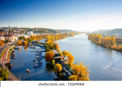 Prague, Czech republic - October 2015: Tranquil sunset  casts long shadows across the Vitava, a forest of gold stretches into the hazy distance. Panoramic views of the River Vitava from Vysehrad