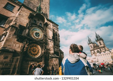 PRAGUE, CZECH REPUBLIC - OCTOBER 9, 2014: The unrecognizable man and boy are looking at astronomical clock in Prague. Tower of town hall with astronomical clock, or Prague orloj in Prague