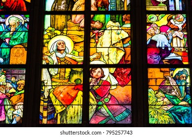 Prague, Czech Republic - October 9, 2017: Stained glass window by painter Alphonse Mucha in St. Vitus Cathedral, portrays St. Wenceslas with his grandmother St. Ludmila surrounded by other saints.