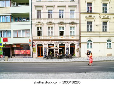 PRAGUE CZECH REPUBLIC - SEPTEMBER 1; City street scenes and buildings people outside Le Petit Cafe beside Chinese restaurant while women in red crosses road September 1 2017 Prague Czech Republic