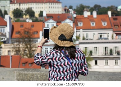 Prague, Czech Republic, September 17, 2018. A woman in a hat takes pictures on a mobile phone in the city